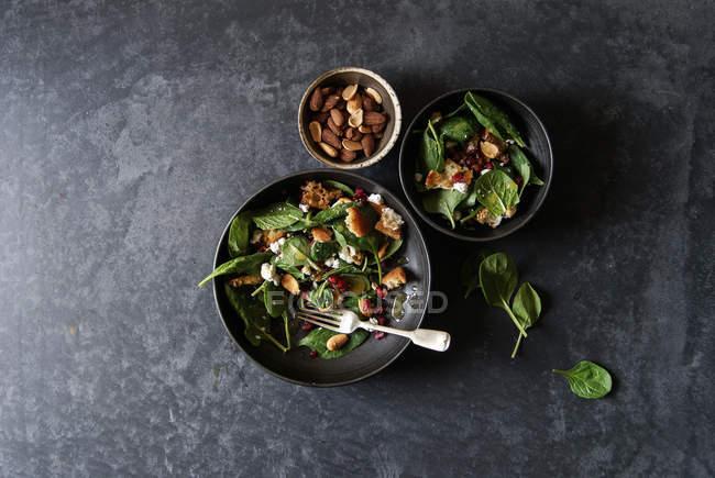Salat mit Gemüse, Käse und Mandeln in Schalen auf grauer Oberfläche — Stockfoto