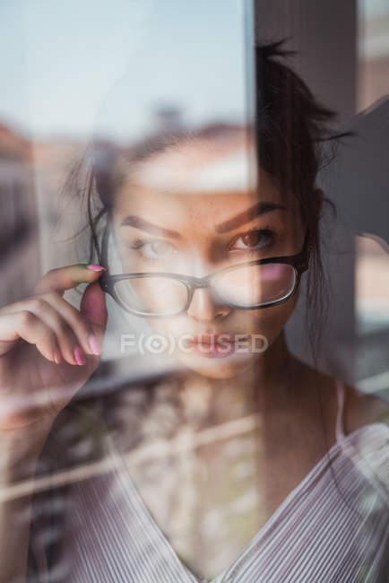 Femme sensuelle avec des lunettes regardant la caméra derrière la fenêtre — Photo de stock