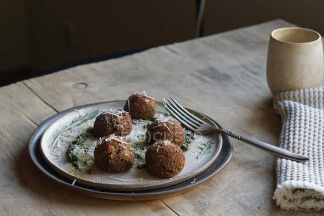Boulettes de viande aux lentilles garnis de sauce pesto de roquette et fromage sur la plaque sur la table en bois — Photo de stock