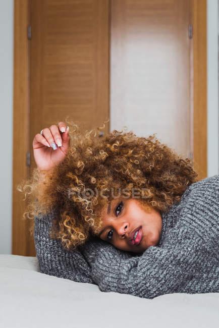 Этническая женщина в сером свитере лежит на кровати и смотрит в камеру — стоковое фото