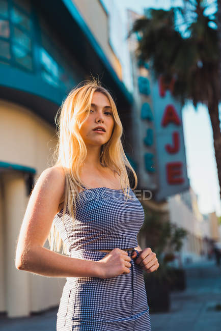 Young woman in stylish outfit looking at camera while standing on blurred background of street — Stock Photo