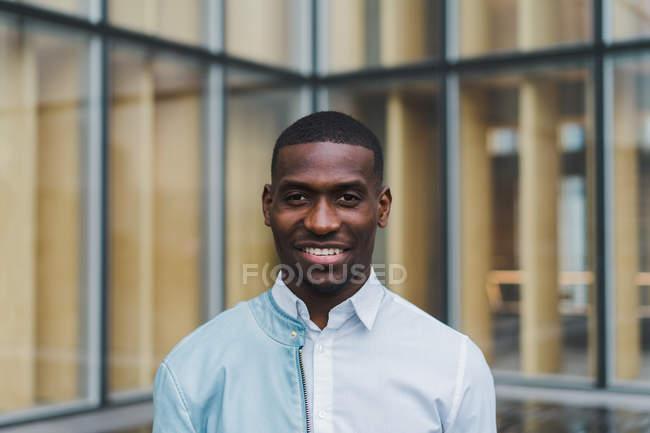 Jeune homme ethnique en chemise blanche et veste en cuir léger sur une épaule debout contre un bâtiment moderne en verre — Photo de stock