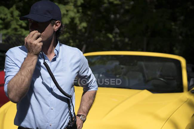 Homem falando no rádio definido fora na frente do carro amarelo moderno — Fotografia de Stock