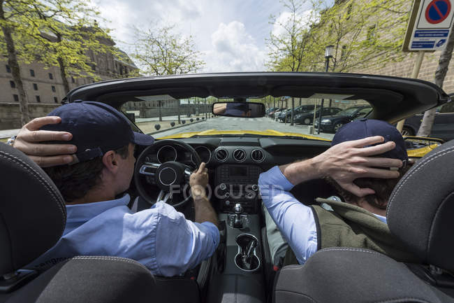 Back view of two men driving in modern fast car down city road in sunlight — Stock Photo