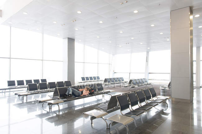 Tourist woman lying and resting on bench in terminal in airport — Stock Photo