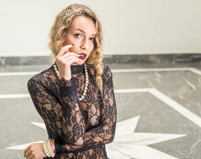 Portrait of elegant woman in black lace dress touching lips — Stock Photo