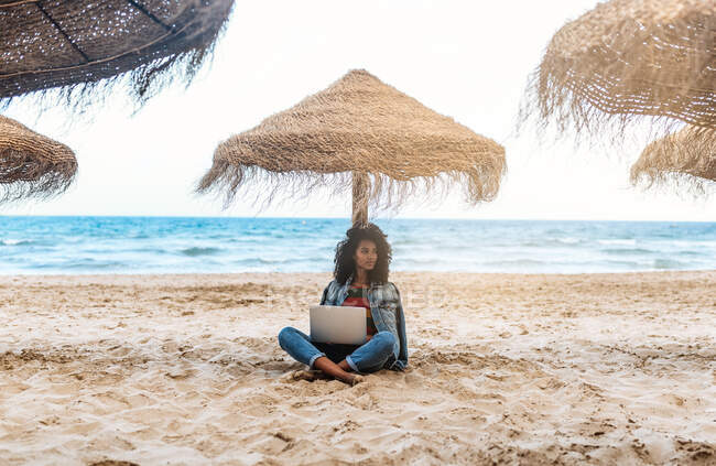 Mulher se apoiando em um guarda-chuva de palha na praia trabalhando no computador — Fotografia de Stock