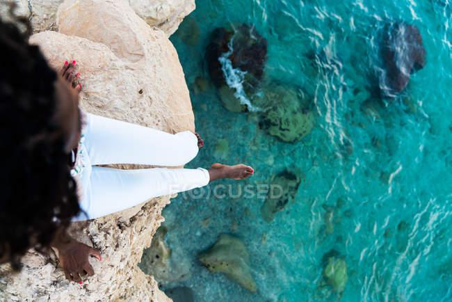 Жінка, сидячи на скелі над кришталево чисте бірюзові води — стокове фото