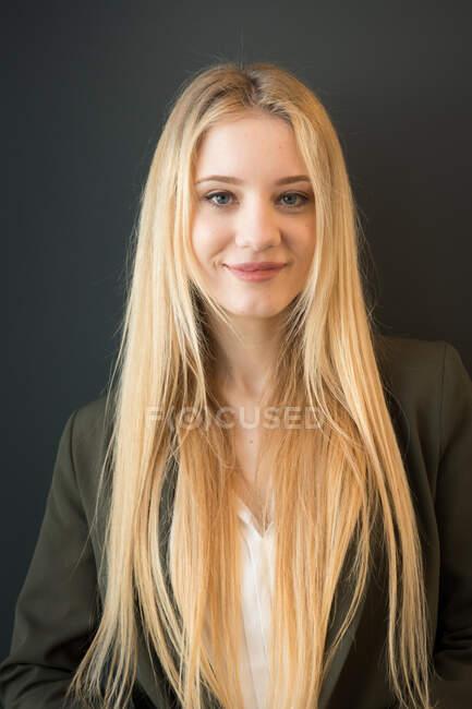 Hermosa joven rubia en traje oscuro elegante de pie con confianza con los brazos cruzados y mirando a la cámara sonriendo sobre fondo negro - foto de stock