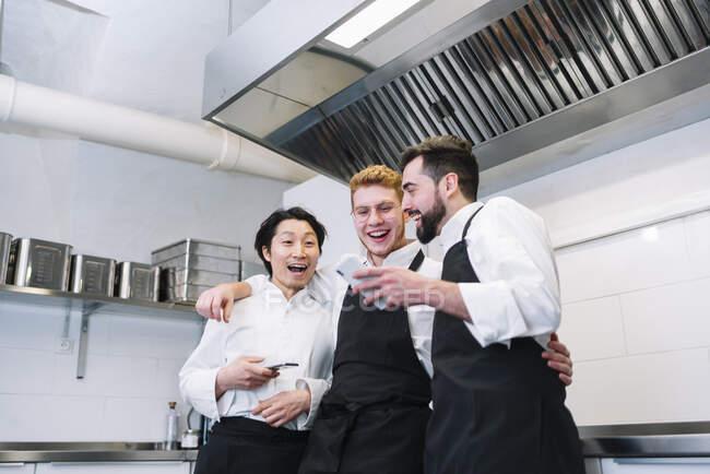 Trois hommes divers en uniforme de cuisine riant et naviguant smartphones tout en se tenant sur la cuisine du restaurant ensemble — Photo de stock