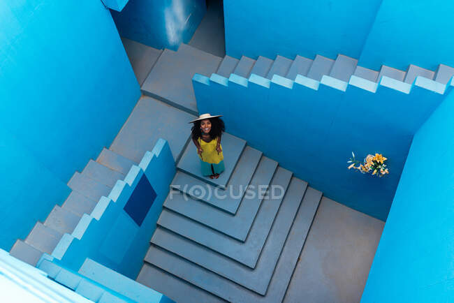 Black woman in a blue building stairs with a straw hat — Stock Photo