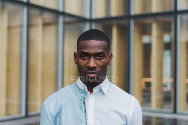 Grave giovane uomo etnico in camicia bianca e giacca di pelle leggera su una spalla in piedi contro vetro edificio moderno — Foto stock
