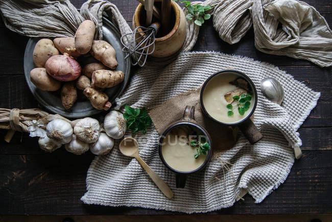 Миски смачний суп топінамбур з інгредієнти на сільському дерев'яний стіл — стокове фото