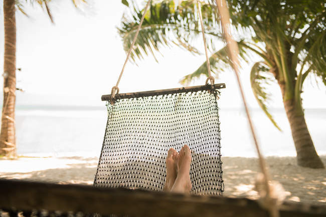 Legs of unrecognizable woman lying in hammock at tropical seaside — Stock Photo