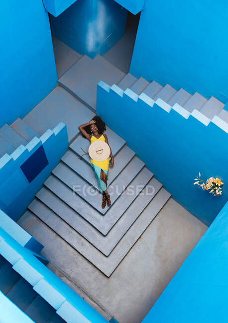 Black woman lying down in a blue building stairs — Stock Photo