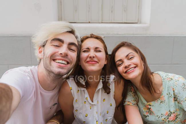 Heureux jeunes amis posant contre le mur sur la rue — Photo de stock