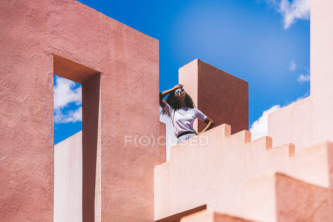 Black woman in a colorful geometric building with sunglasses — Stock Photo