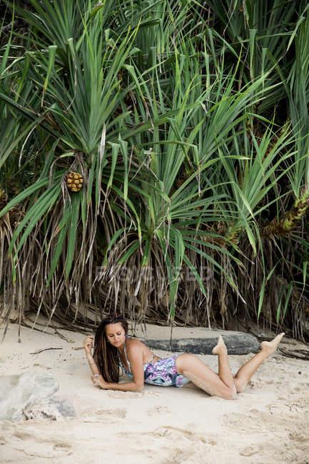 Giovane donna in costume da bagno che si trova sulla sabbia sulla spiaggia tropicale — Foto stock