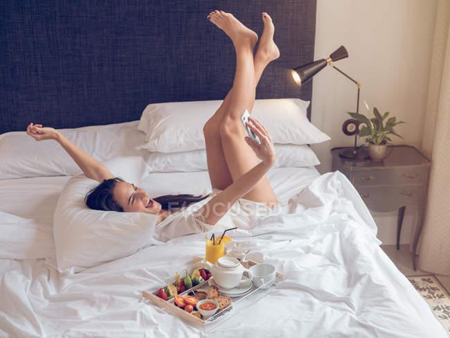 Женщина делает селфи в постели — стоковое фото
