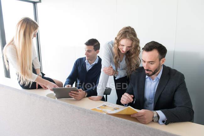 Vue de côté de la longue table avec quelques groupes de coworking utilisant des gadgets et créant un nouveau plan de projet — Photo de stock