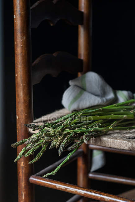 Close-up of bunch of fresh green asparagus on chair on black background — Stock Photo