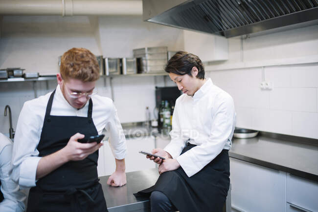 From below shot of two guys in cook uniform standing on restaurant kitchen and browsing smartphones during break — Stock Photo