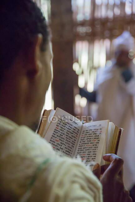 Відверто кажучи, анонімний парафіянин читає молитовник про розмите церковне походження. — стокове фото