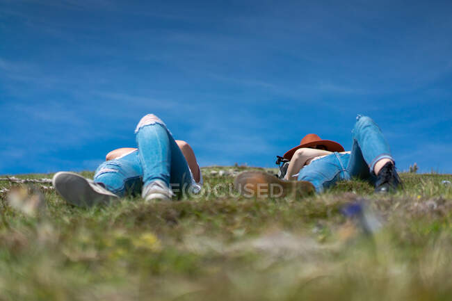 View of women in denim lying on green grass of meadow and sunbathing in summer sunshine under blue sky — Stock Photo