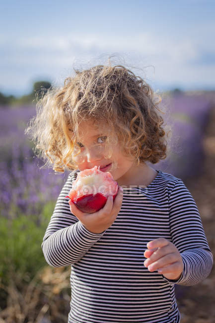 Charming little girl eating juicy peach and looking at camera in field — Stock Photo