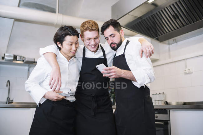 Three diverse men in cook uniform laughing and browsing smartphones while standing on restaurant kitchen together — Stock Photo
