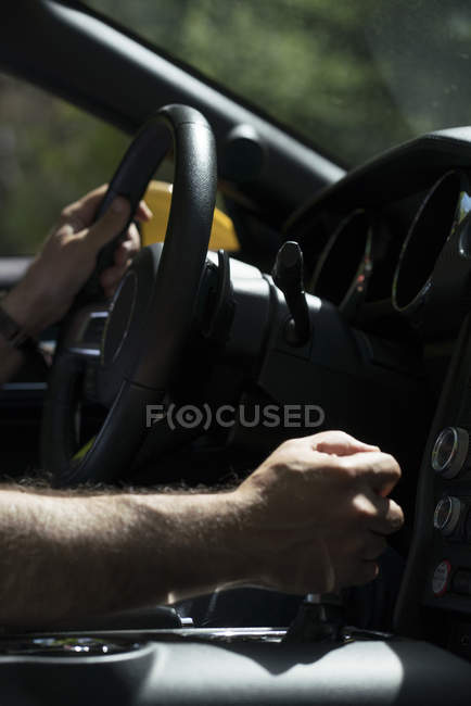 Male hand on steering wheel while driving modern luxury car and hand on transmission control lever — Stock Photo