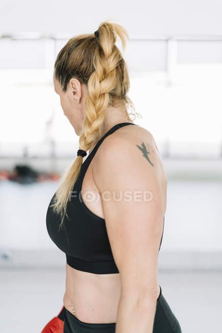 Blondine in Sportbekleidung steht auf verschwommenem Hintergrund des Fitnessstudios und schaut weg — Stockfoto