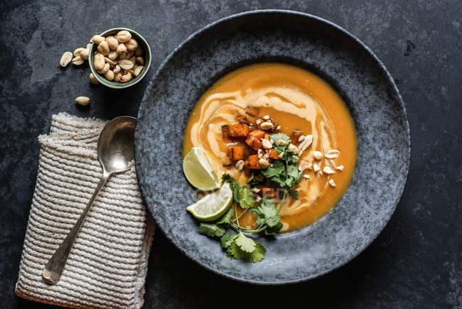 Sopa de calabaza tailandesa con limas y cacahuetes en plato gris sobre superficie gris - foto de stock