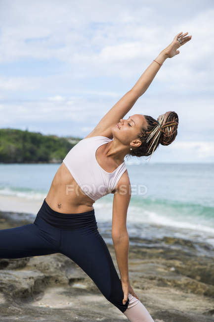 Young fit woman stretching at seaside during yoga — Stock Photo