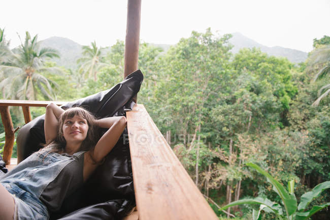 Young woman lying on terrace in tropical forest and looking away — Stock Photo