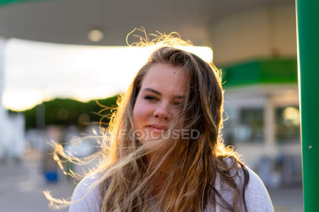 Happy young woman in casual outfit looking at camera and laughing in back lit of sunset light — Stock Photo