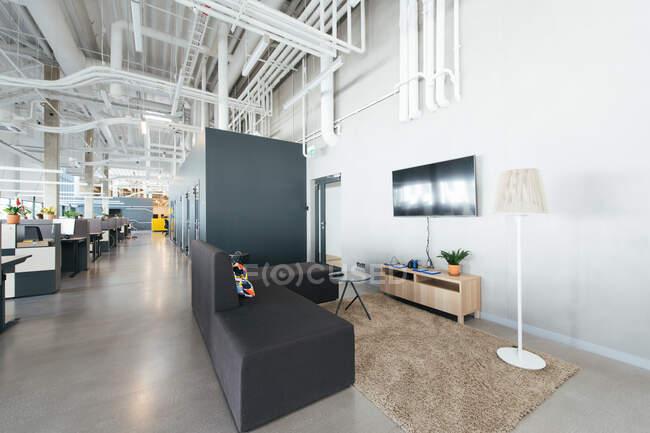 Imagen interior de una nueva oficina de espacio abierto con muebles coloridos en el lugar de trabajo y luz desde ventanas - foto de stock