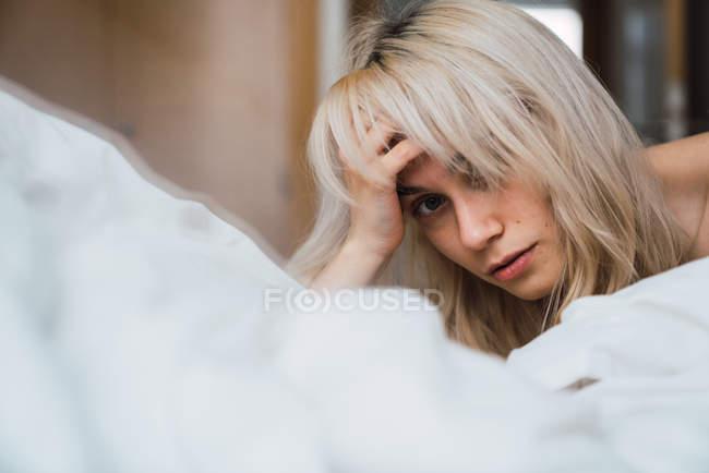 Mulher loira deitada em uma cama confortável no quarto aconchegante — Fotografia de Stock