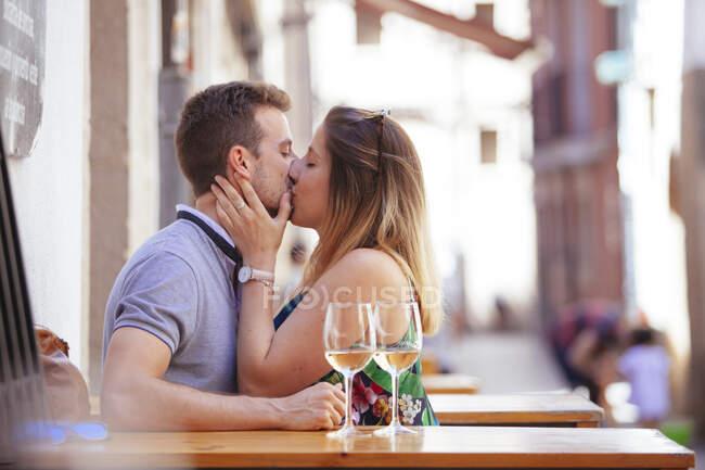 Vue latérale d'un couple passionné assis à table à l'extérieur du restaurant avec des verres de vin et des baisers — Photo de stock
