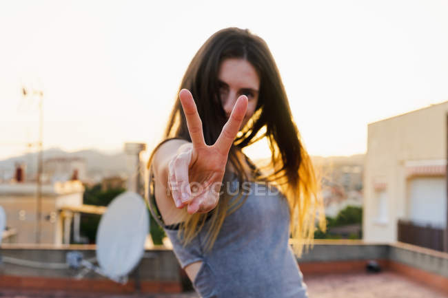 Happy woman showing two fingers outdoors at sunset — Stock Photo