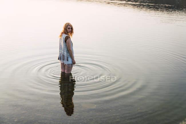 Молода жінка, стоячи в прозорій воді озера і дивитися через плече в (літо) — стокове фото