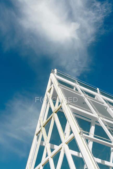 Techo de cristal pendiente bajo el cielo azul - foto de stock