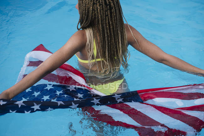 Вид сзади женщины, стоящей в бассейне с американским флагом — стоковое фото