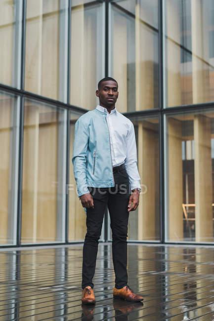 Calme élégant homme ethnique debout contre le bâtiment en verre et en regardant la caméra — Photo de stock
