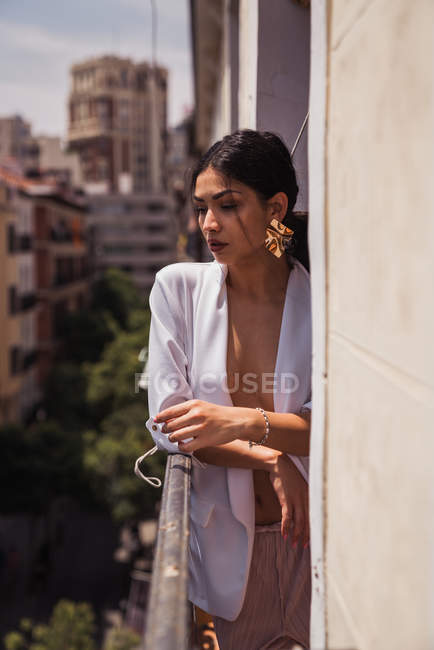 Alluring brunette woman in elegant white jacket and golden earrings leaning on balcony fence — Stock Photo