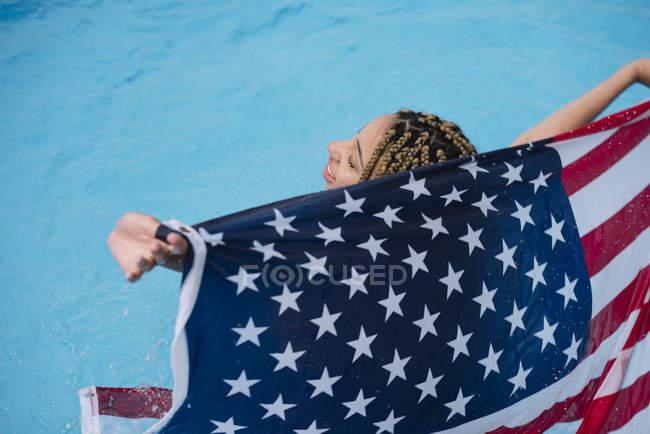 Donna sorridente all'interno tenendo bandiera americana in piscina — Foto stock