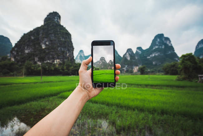 Human hand taking photo of rice fields and unique mountains, Guangxi, China — Stock Photo