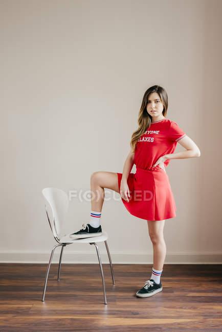 Девушка в красном наряде позирует с одной ногой на стуле — стоковое фото