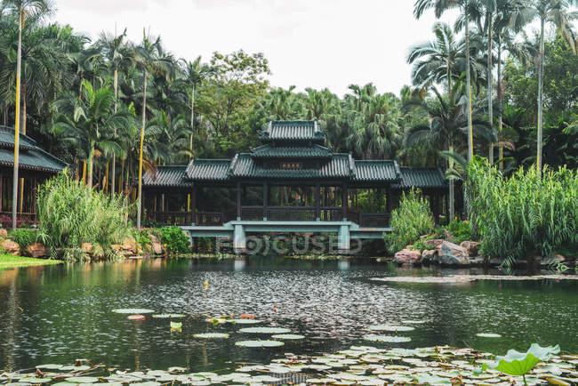 Edifício oriental velho no lago no parque tropical, Nanning, China — Fotografia de Stock