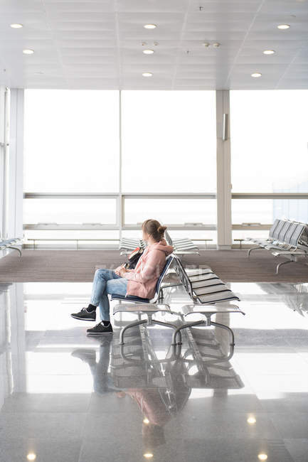 Tourist woman sitting on bench in terminal in airport — Stock Photo